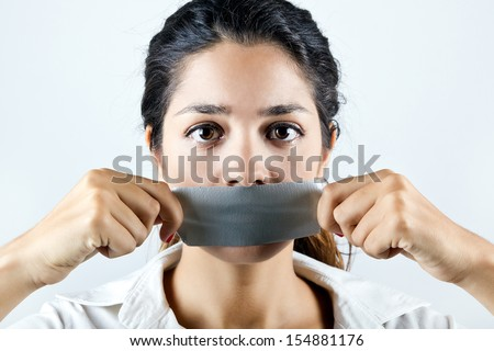 Young woman with mouth covered with tape. Concept of forbidden opinion - stock photo