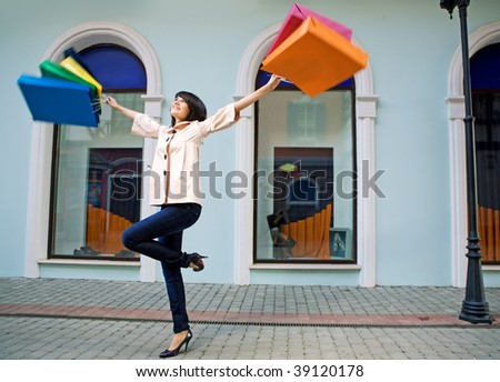 young woman with multi-coloured bags with purchases - stock photo