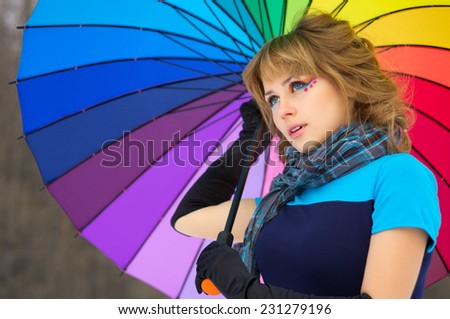 Young woman with multicolor umbrella at winter forest - stock photo