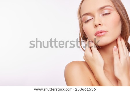 Young woman with natural makeup touching her face