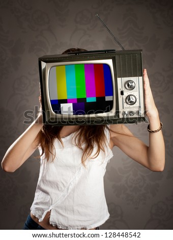 young woman with old retro television on her head - stock photo