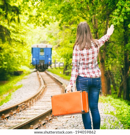 young woman with old suitcase waving his hand, departing train on background - stock photo