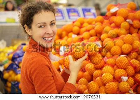 young  woman with oranges in store - stock photo