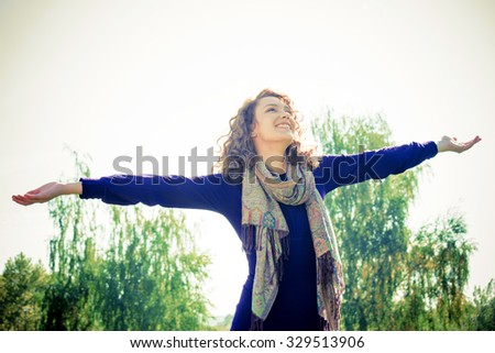 Young woman with outstretched hands enjoying outdoors - stock photo