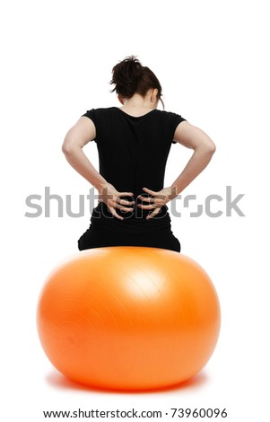 young woman with pain in the back sitting on orange exercise ball - stock photo