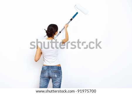 Young woman with paint brushes doing renovation and white wall - stock photo