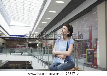 Young woman with paper bag looking up in shopping centre - stock photo