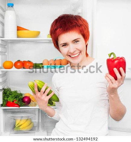 young woman with papper and cucumbers against the refrigerator with food