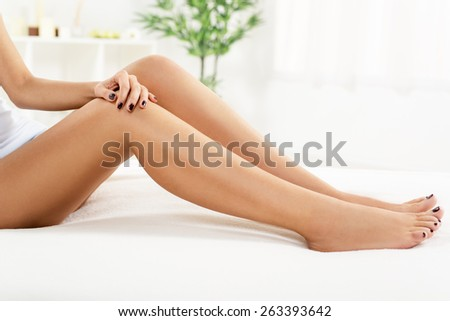 Young woman with perfect legs sitting and relaxing at home.