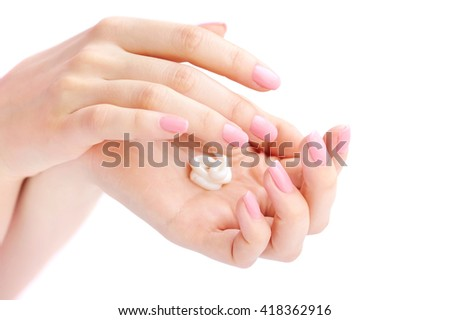 Young woman with pink manicure applies cream on her hands - stock photo