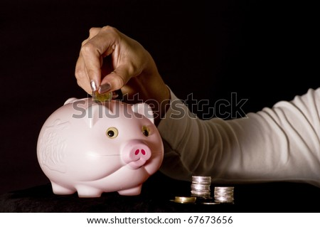 young woman with pink piggy bank - stock photo