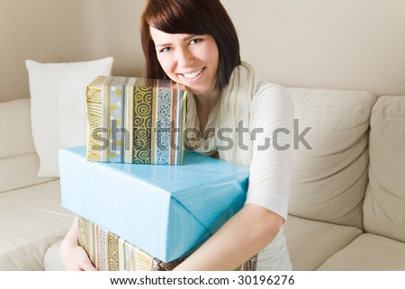 Young woman with presents in her living room - stock photo