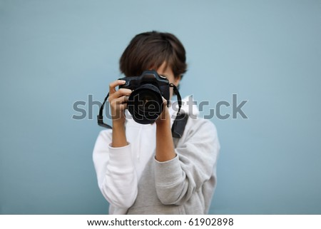 young woman with professional camera, selective focus on nearest part of lens - stock photo