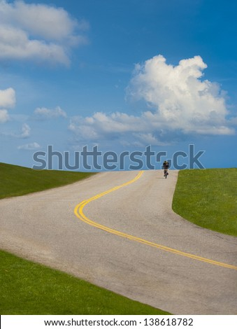Young woman with raised arms happily hiking up hill along a curving paved path. - stock photo