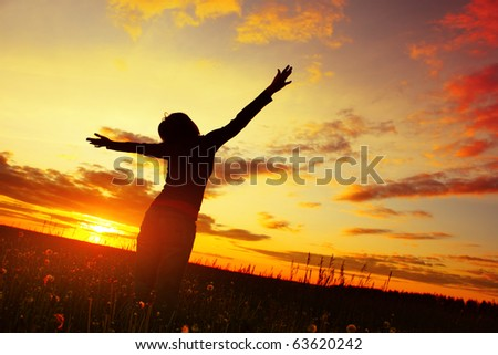 Young woman with raised hands standing on meadow with herbs on sunset - stock photo