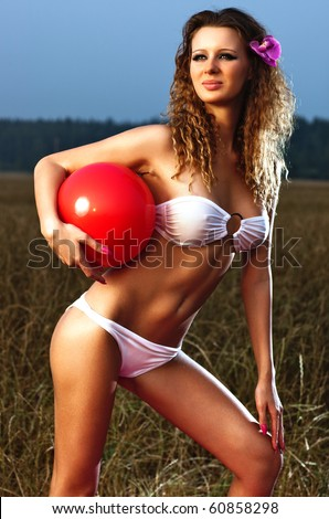 Young woman with red ball outdoors. - stock photo