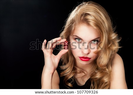 Young woman with red dice on black background - stock photo