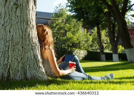 Young woman with red disposable paper cup of coffee using tablet pc under the tree on a green lawn in a park