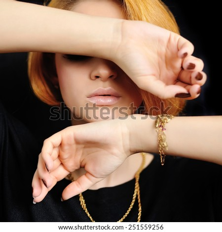 Young woman with red hair closes eyes hand
