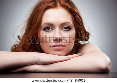 Young woman with red hair portrait. On gray wall background. - stock photo