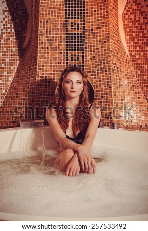 Young woman with red hair take bubble bath with candle. - stock photo