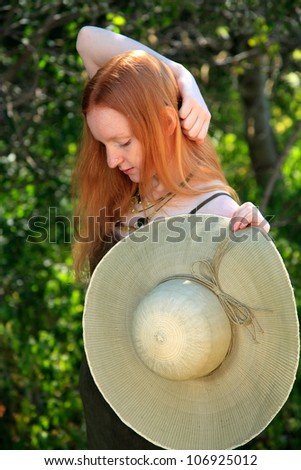 Young Woman With Red Hair Wearing A Sundress And Hat Outdoors