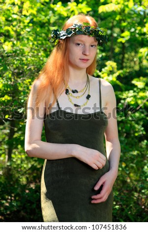 Young Woman With Red Hair Wearing A Sundress And Ivy Headdress Outdoors