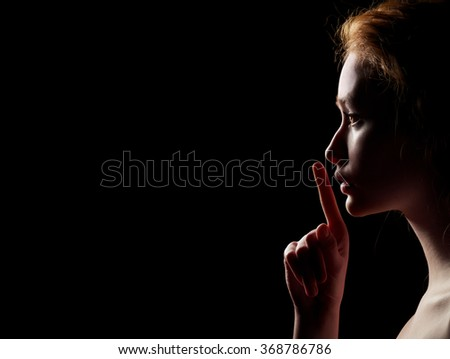 Young Woman With Red Hairs Gesturing For Being Quiet, Shows Silence Sign In Dark Background With Copyspace - stock photo