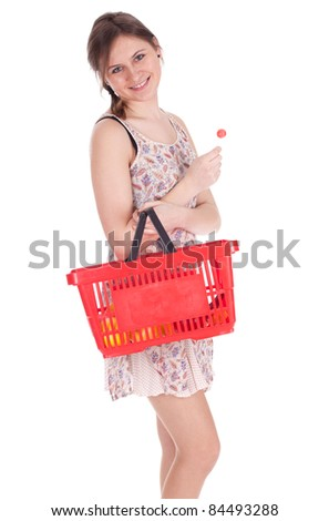 young woman with red shopping basket keeping lollipop - stock photo