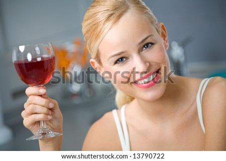 Young woman with red wine at kitchen
