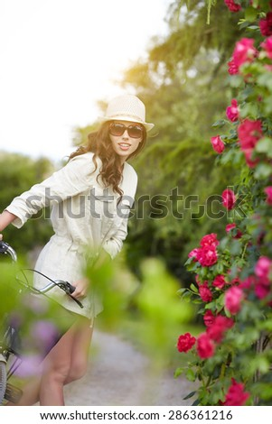 Young woman with retro bicycle in a garden- outdoor portrait - stock photo