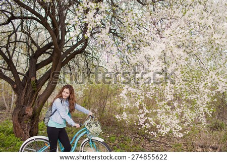 Young woman with retro bicycle in a park - under a blossoming tree
