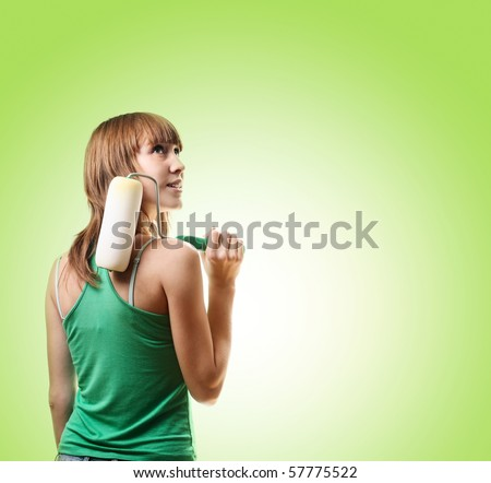 Young woman with roller brush over green background