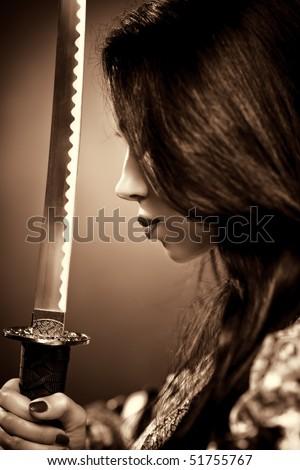 Young woman with samurai sword. Sepia color. - stock photo