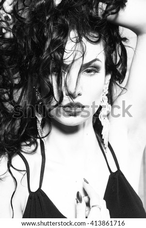 Young woman with sexy face in diamond earrings with stylish hairdo, black and white