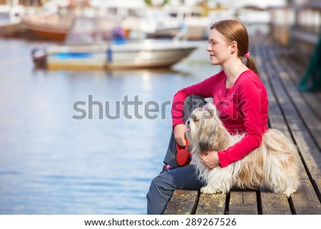 Young woman with shih-tzu dog sitting on town quay with boats. - stock photo
