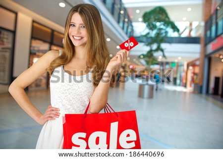 Young woman with shopping bag and card in store - stock photo