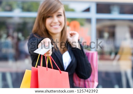 Young woman with shopping bags and credit card - stock photo