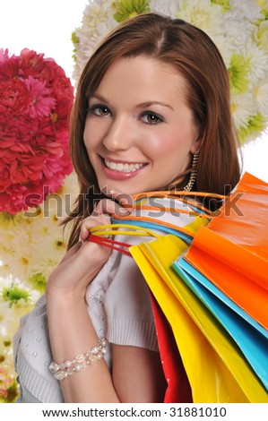 Young woman with shopping bags and flowers on the background