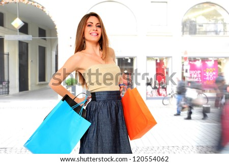 Young woman with shopping bags at the mall - stock photo