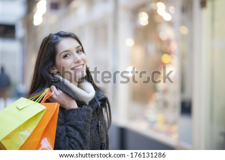 young woman with shopping bags, shops lights in background - stock photo