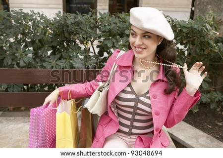 Young woman with shopping bags, sitting on a bench in a shopping street. - stock photo
