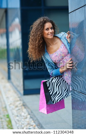 young woman with shopping bags smiling and having fun