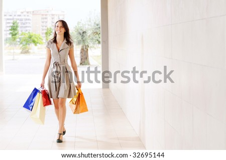 young woman with shopping bags, smiling and  walking - stock photo