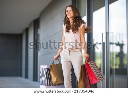 Young woman with shopping bags walking out from shop - stock photo