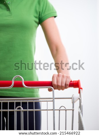 Young woman with shopping cart at supermarket hands close-up.