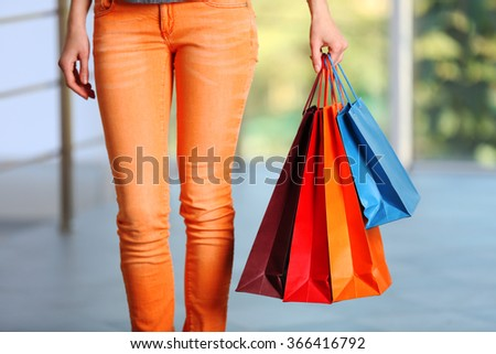 Young  woman with shopping packages on defocused background - stock photo