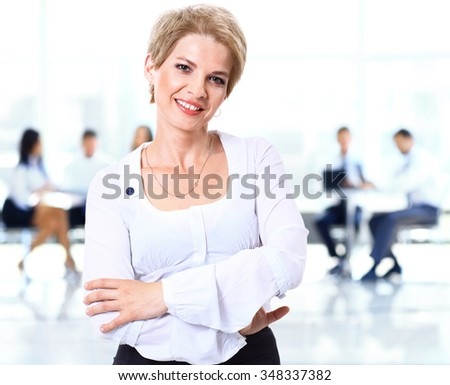 young woman with short hair smiling on the background of office colleagues - stock photo