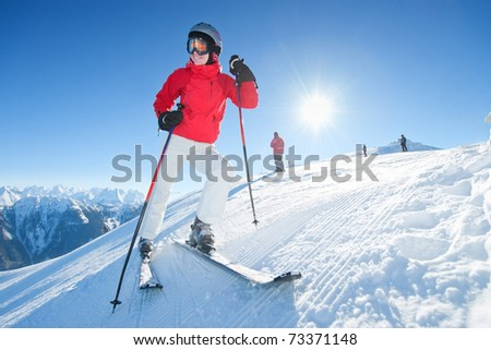 Young woman with ski stand at tom of the hill - stock photo