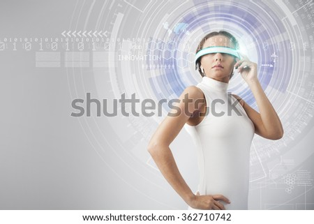 Young woman with smart-glasses front of virtual future interface - stock photo